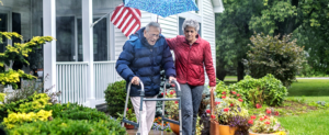 Woman helping older man walk in the rain